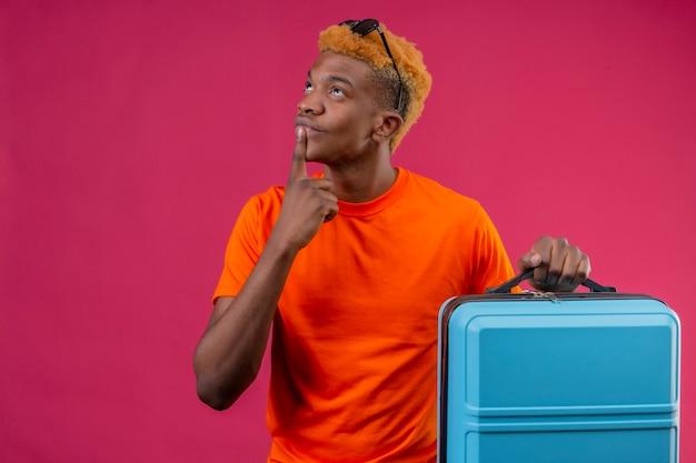 顔の思考に物思いに沈んだ表情で見上げる旅行スーツケースを持ってオレンジ色のtシャツを着ている若いハンサムな男の子