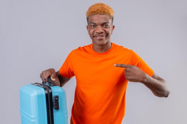 それを指で指している旅行スーツケースを保持しているオレンジ色のtシャツを着ている若いハンサムな男の子
