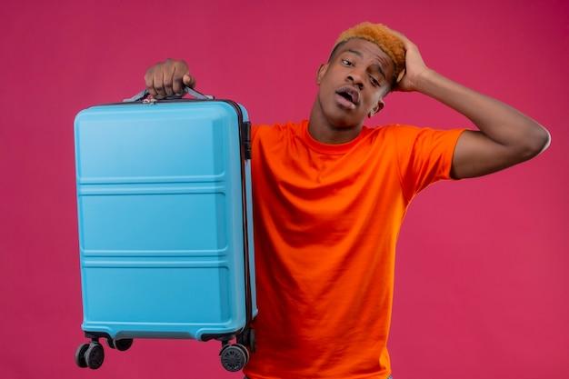 ピンクの壁の上で混乱して探している間違いのため彼の頭に手で立っている旅行スーツケースを保持しているオレンジ色のtシャツを着ている若いハンサムな男の子