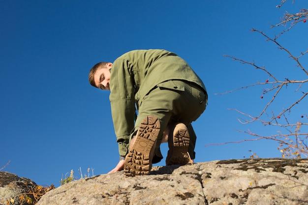 カメラを見ながら大きな岩に登る若いハンサムな男の子のスカウト。青い空の背景にキャプチャされます。