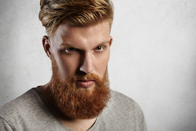 Young handsome and brave man   from under his blond eyebrows. european hipster in grey top with round crewneck, with nice ginger beard and moustaches looks stylish and trendy.