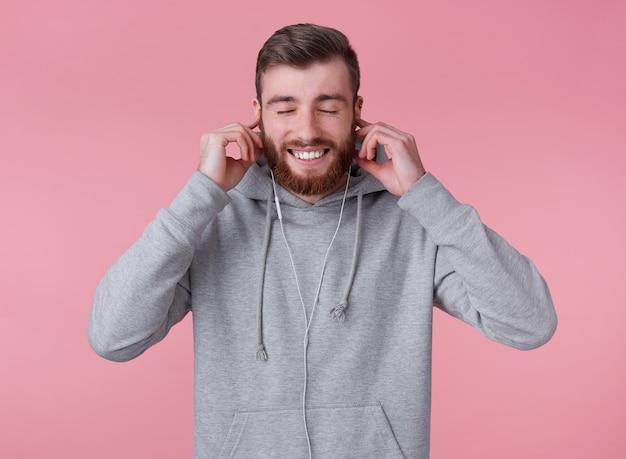 Молодой красивый широко улыбающийся рыжий бородатый мужчина в серой толстовке с капюшоном выглядит счастливым и довольным, слушая свою любимую песню в наушниках, стоит на розовом фоне с закрытыми глазами.