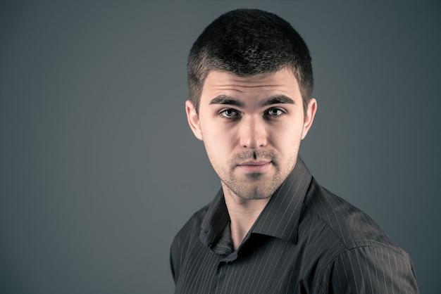 暗い壁にポーズをとって若いハンサムな黒髪の男