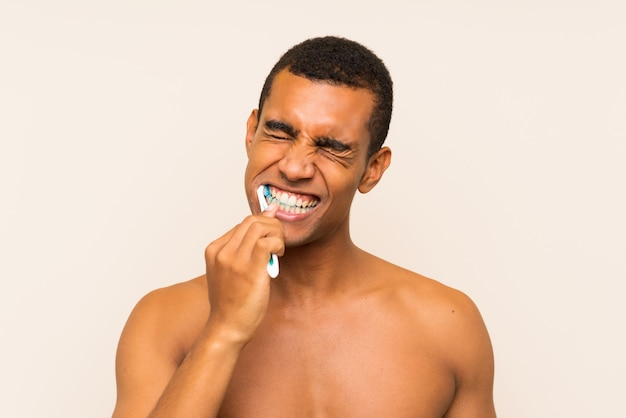 Young handsome brunette man brushing his teeth