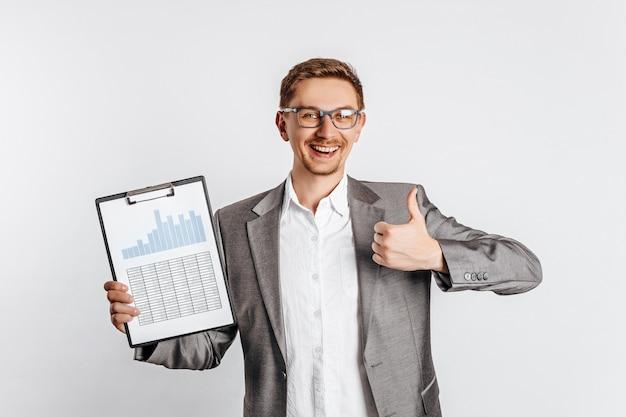 スーツを着た眼鏡をかけた若いハンサムなブルネットの男は微笑んで、白い孤立した空間にビジネス文書とグラフで親指を表示します。