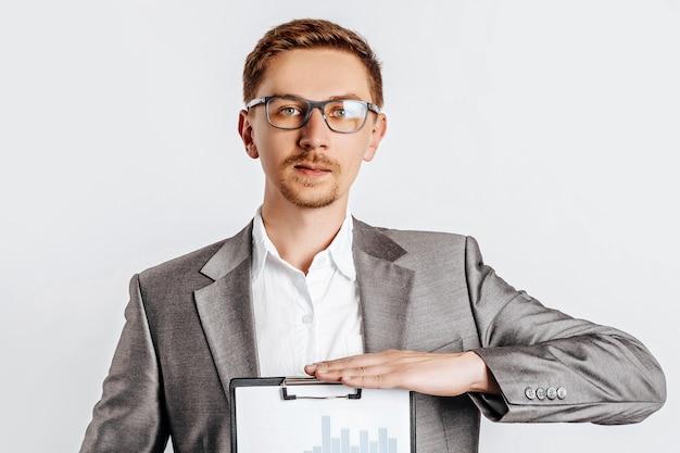 白い孤立した背景の上のビジネス文書やチャートとスーツのメガネの若いハンサムなブルネットの男