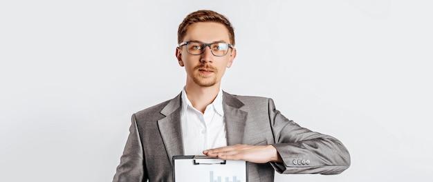 ビジネス文書やチャートとスーツのメガネの若いハンサムなブルネットの男