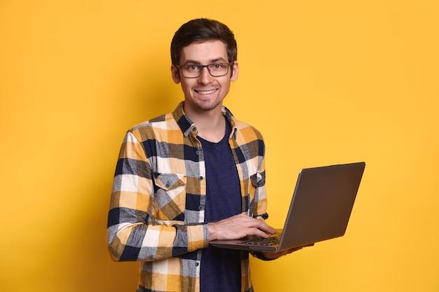 眼鏡をかけて若いハンサムなブルネットの男は、黄色で隔離のラップトップを保持して、幸せに笑っています