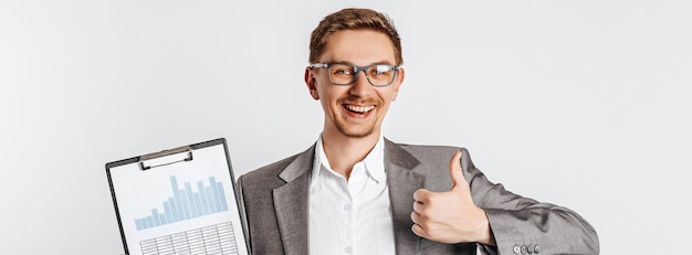 眼鏡をかけた若いハンサムなブルネットの男は微笑んで、灰色の孤立したドキュメントで親指を表示します