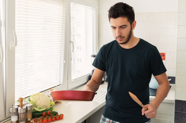 A young handsome brunette man is standing in the kitchen and holding a frying pan in his hands. husband preparing breakfast for his wife.