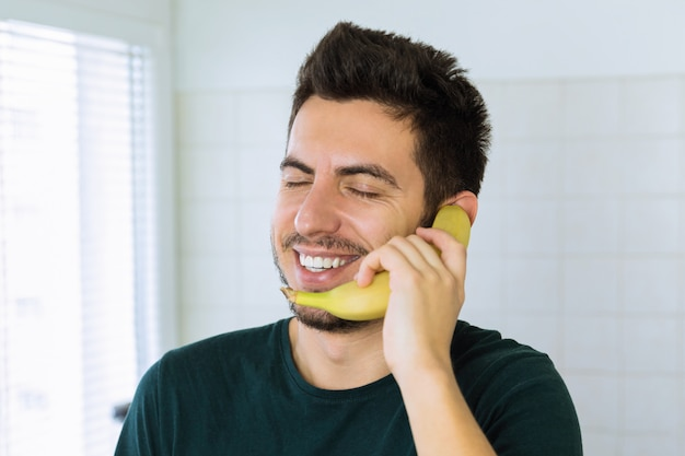 A young handsome brunette man is talking on the phone, instead of using a banana. conceptual photo.