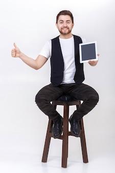 흰색 셔츠와 검은색 조끼를 입은 수염을 기른 젊고 잘생긴 브루네트 남자는 태블릿을 들고 회색 배경에 엄지손가락을 치켜든다.