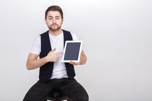 흰색 셔츠에 수염을 기른 젊고 잘생긴 브루네트와 검은색 조끼가 태블릿을 들고 회색 배경의 의자에 앉아 있다