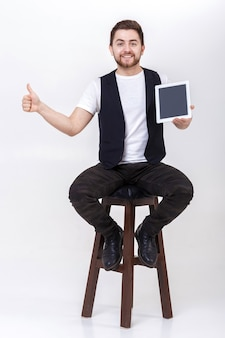 Young handsome brunette man with  beard in white shirt and  black waistcoat holding tablet and showing thumb up sign on gray background