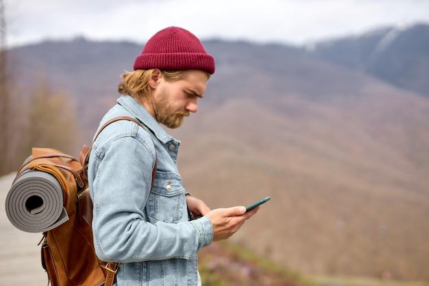 革の茶色のバックパック、秋のスタイル、旅行者、冒険、自由な精神で、スマートフォンを使用して野生の自然を旅する若いハンサムな残忍なひげを生やした男。コピースペース。側面図