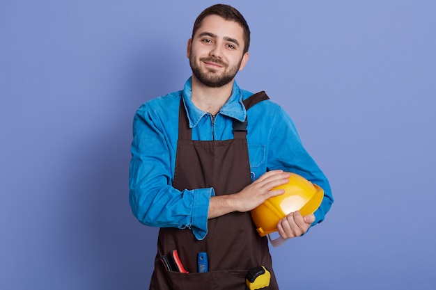Young handsome builder holding yellow helmet in hands, does repairing, wears casual brown apron