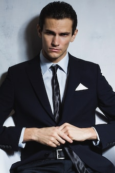 Young handsome business man in black suit sits in chair on grey wall