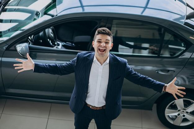 Giovane uomo bello di affari in uno showrrom dell'automobile