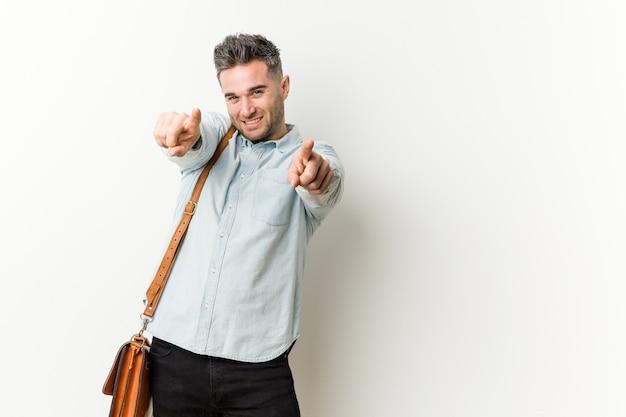 若いハンサムなビジネスマンの陽気な笑顔が正面を指しています。