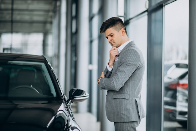 자동차 쇼룸에서 차를 선택하는 젊은 잘 생긴 사업가