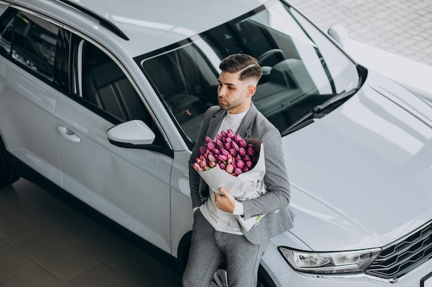 Young handsome business man delivering bouquet of beautiful flowers