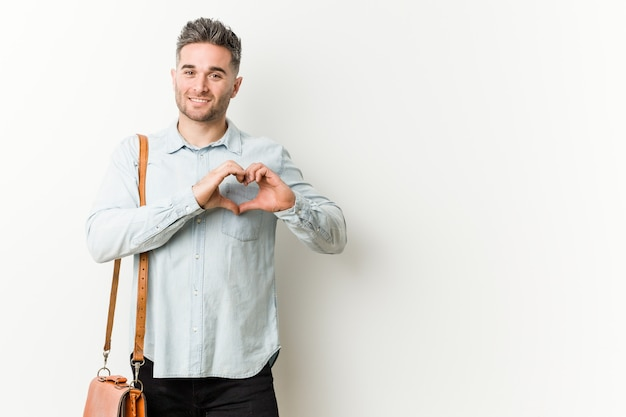 Young handsome business man smiling and showing a heart shape with hands.