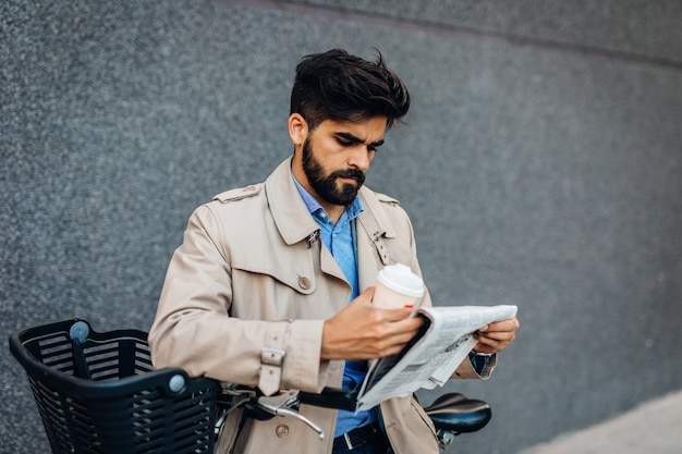 Young handsome business man standing on city street with bicycle, drinking coffeee to go and reading newspaper. environmental protection and ecological transport concept.