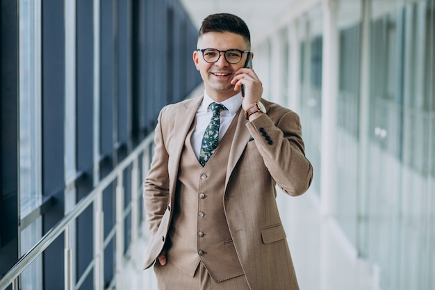Young handsome business man standing with phone at the office