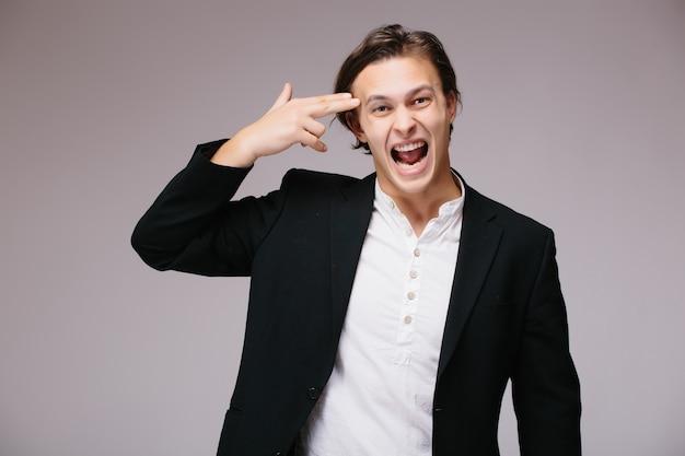 Молодой красивый деловой человек в костюме и галстуке над изолированной стеной, стреляя и убивая себя, указывая рукой и пальцами на голову, как пистолет