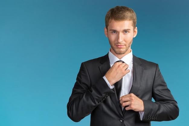 Young handsome businessman adjusting his tie