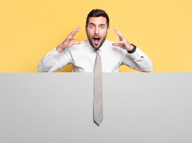 灰色のプラカードに驚いた若いハンサムなビジネスマン