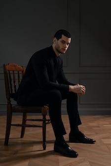 Giovane imprenditore bello in camicia nera e abito nero