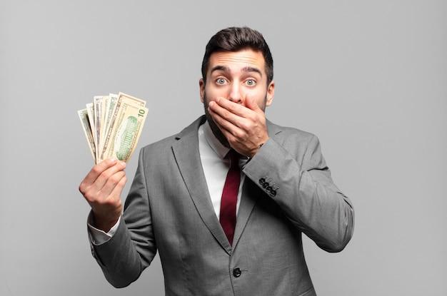 Молодой красивый бизнесмен закрыл рот руками с шокированным, удивленным выражением лица