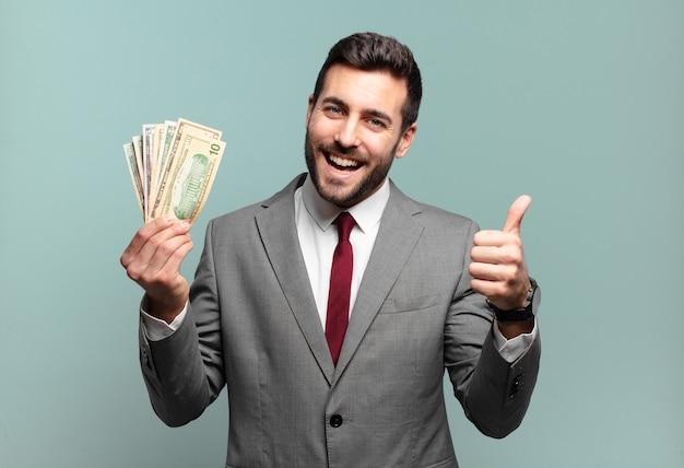 若いハンサムなビジネスマンは、誇り、のんき、自信を持って幸せを感じ、親指を立てて前向きに笑っています