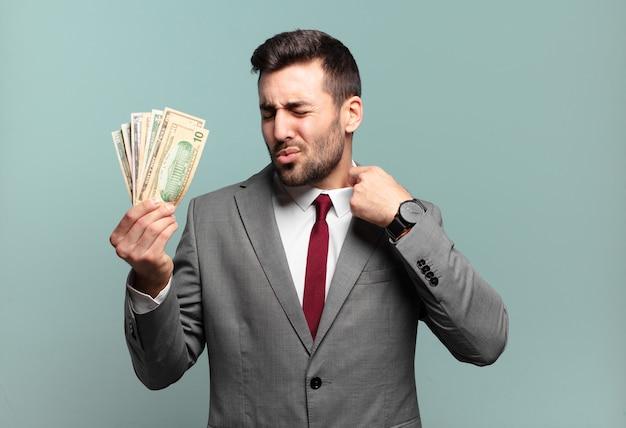 젊은 잘 생긴 사업가 스트레스, 불안, 피곤하고 좌절감을 느끼고, 셔츠 목을 당기고, 문제로 좌절감을 느낍니다. 청구서 또는 돈 개념