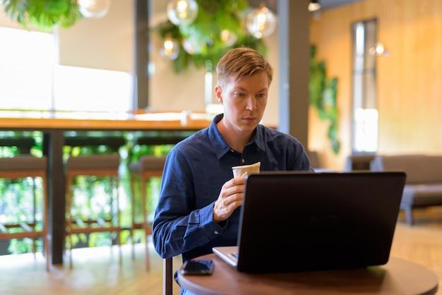 コーヒーショップでノートパソコンを使用しながらコーヒーを保持している若いハンサムなビジネスマン