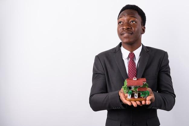 Молодой красивый бизнесмен, держащий фигурку дома на белом