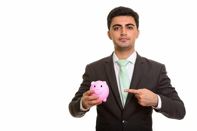 貯金箱とポインティを保持している若いハンサムなビジネスマン
