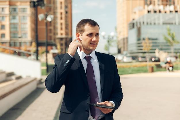 スーツを着た若いハンサムなビジネスマンは、ヘッドフォンで話し、笑顔です。仕事。
