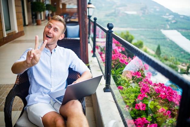 Молодой красивый бизнесмен в белой рубашке и шортах сидит с ноутбуком в кафе за столом. работайте во время отдыха