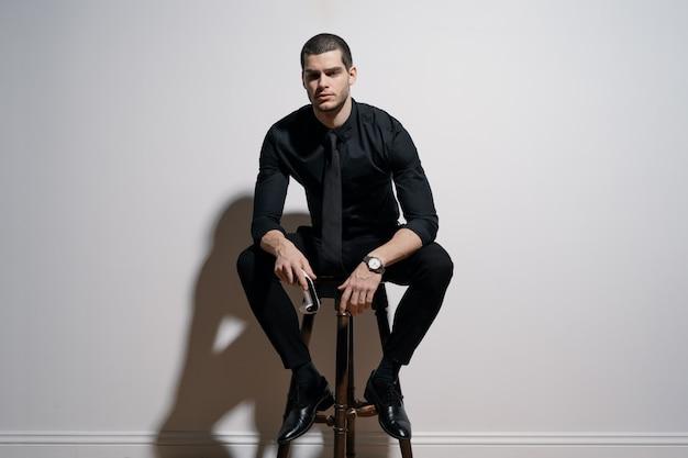 검은 셔츠와 검은 양복에 젊은 잘 생긴 사업가