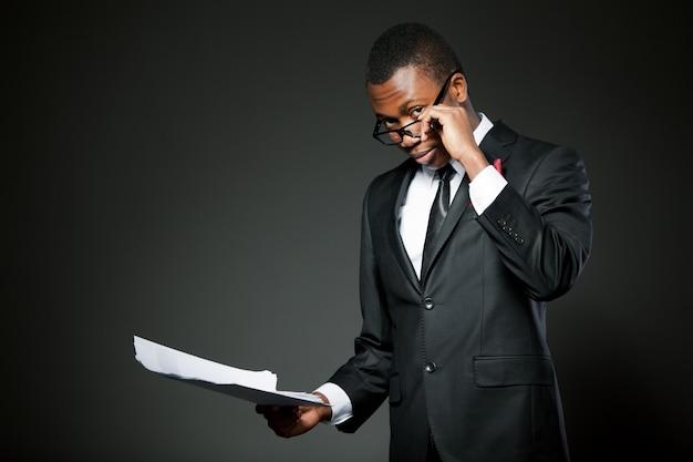灰色の衣装、白いシャツ、ネクタイ、メガネ立って、紙documetsを読んで若いハンサムなビジネスマン