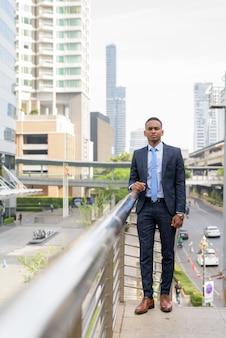 屋外の近代的な建物の眺めに対してスーツを着た若いハンサムなビジネスマン