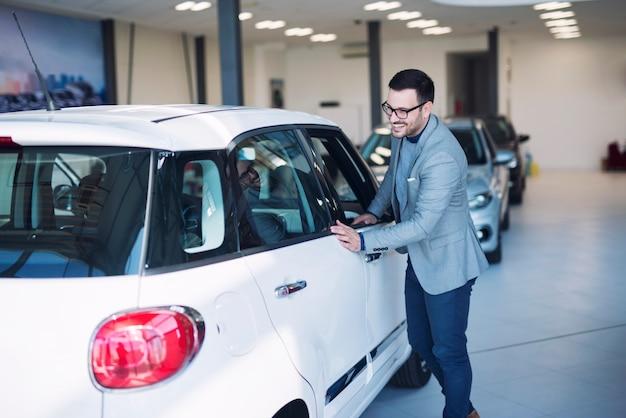 車のディーラーで新しい車を買うスーツの若いハンサムなビジネスマン。