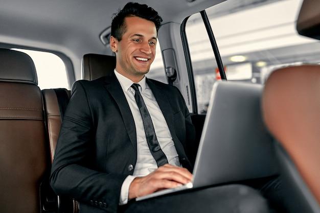 젊은 잘 생긴 사업가 럭셔리 자동차에 앉아있다. 정장을 입은 남자는 여행 중에 노트북을 사용하고 있습니다.