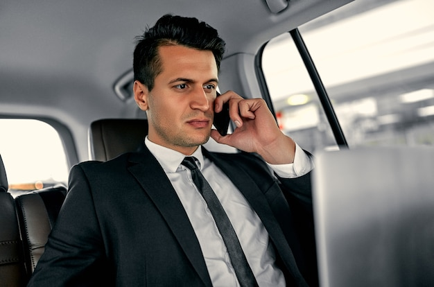 젊은 잘 생긴 사업가 럭셔리 자동차에 앉아있다. 정장에 심각한 잘 생긴 남자는 노트북으로 작업하고 여행에있는 동안 스마트 폰으로 이야기합니다.