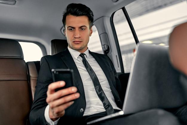 Молодой красивый бизнесмен сидит в роскошной машине. серьезный мужчина в костюме работает с ноутбуком и смартфоном во время поездки.