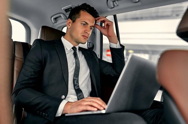 젊은 잘 생긴 사업가 럭셔리 자동차에 앉아있다. 정장에 심각한 남자는 여행에있는 동안 노트북으로 일하고있다.