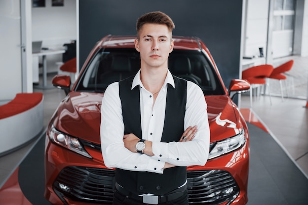 A young handsome businessman is standing by the car