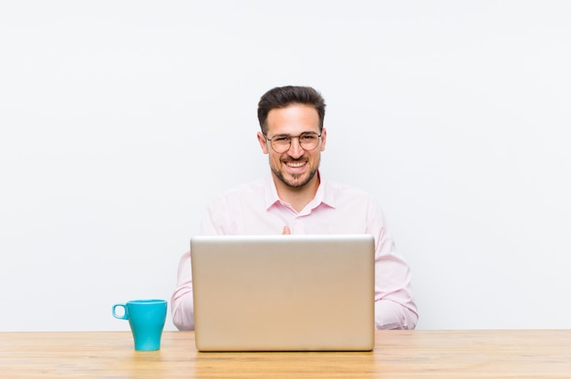 Young handsome businessman laughing out loud at some hilarious joke feeling happy and cheerful having fun